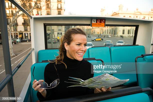 Female tourist sitting on tour bus with street map and sunglasses