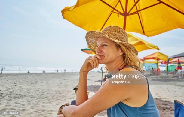 Female tourist sitting under beach umbrella, Camana, Arequipa, Peru