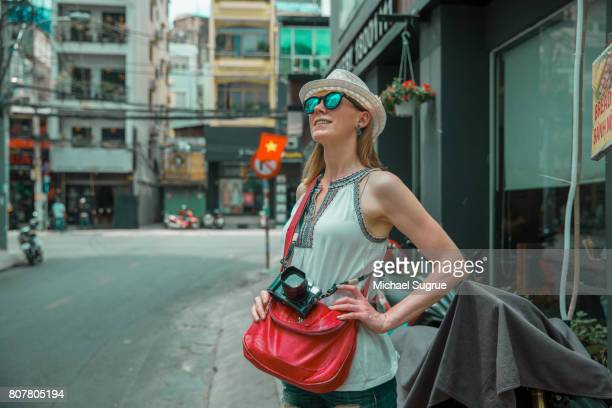 A female tourist stands confidently on a street corner in Ho Chi Minh City, Vietnam.