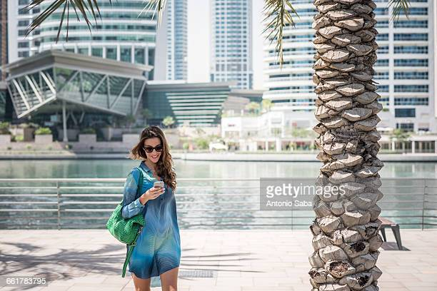 Female tourist strolling on waterfront reading smartphone texts, Dubai, United Arab Emirates