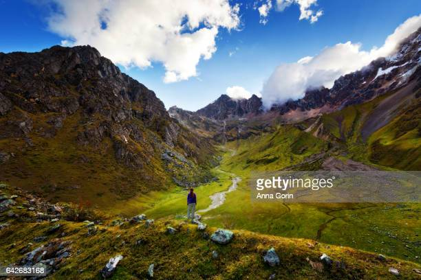 Female tourist takes in view of lush valley surrounded by snowcapped mountains above Humantay Lake along Salkantay Trek to Machu Picchu, Peru