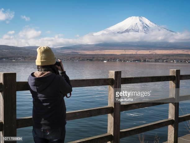 female tourist taking a photo of mt. fuji at lake yamanaka - fuji hakone izu national park stock photos and pictures