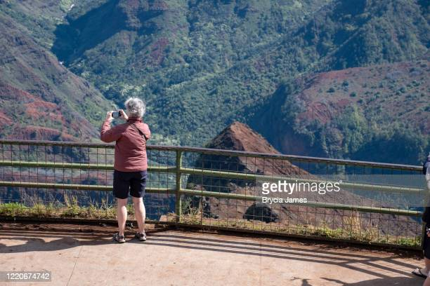 a female tourist taking a photo of waimea canyon - brycia james stock pictures, royalty-free photos & images