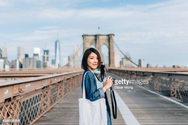 Female tourist taking picture on Brooklyn Bridge