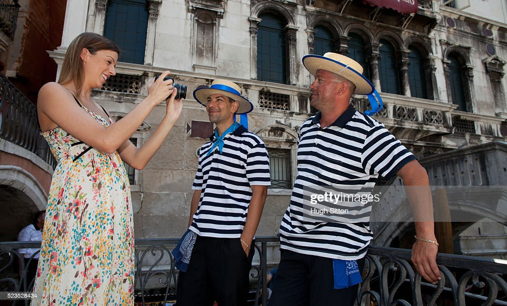 Female tourist taking pictures of gondola drivers, Venice, Italy : Stock Photo