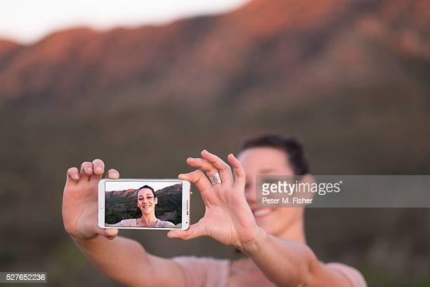 Female tourist taking selfie with Flinders Rangers in background, Australia