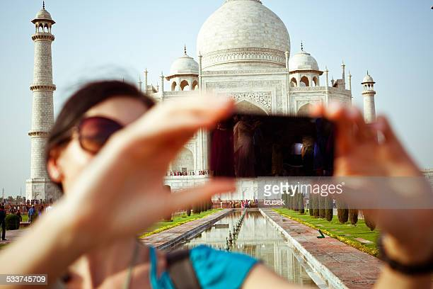 Female tourist taking selfie with Taj Mahal