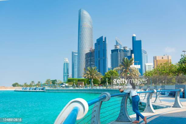 female tourist visiting abu dhabi downtown corniche area and enjoying the view - abu dhabi stock pictures, royalty-free photos & images