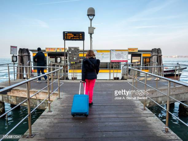 female tourist waiting in a vaporetto stop with her suitcase., venice - nationell sevärdhet bildbanksfoton och bilder