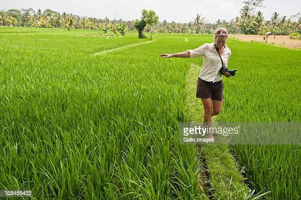 Female tourist walking along grass wall between two rice paddies near Ubud, Bali, Indonesia