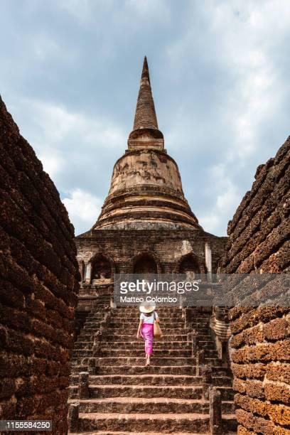 female tourist walking on stairway, si satchanalai, thailand - sukhothai stockfoto's en -beelden