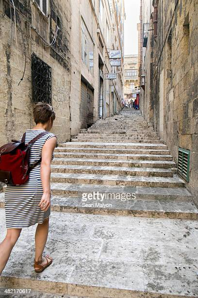 Female tourist walking up stairs, Valletta, Malta