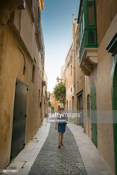 female tourist walking, victoria, gozo, malta - sean malyon stock pictures, royalty-free photos & images