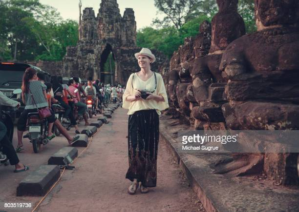 Female tourist walks among statues at sunset near Bayon Temple, near Angkor Wat, Siem Reap, Cambodia.
