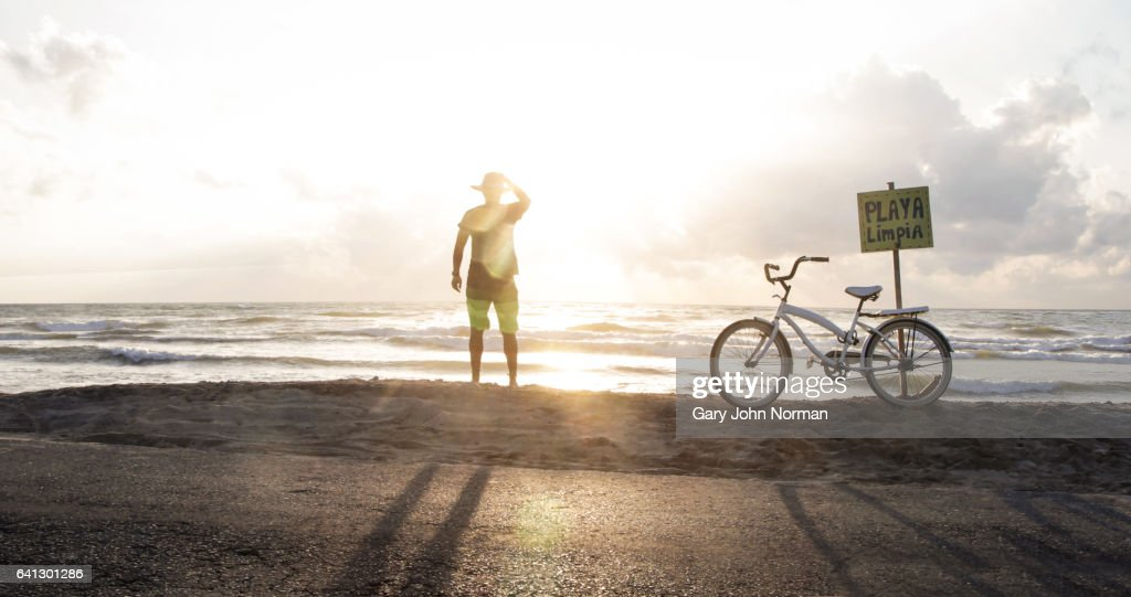 Female tourist with bike stops to watch sunrise over the ocean. : Stock Photo