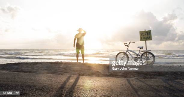 Female tourist with bike stops to watch sunrise over the ocean.