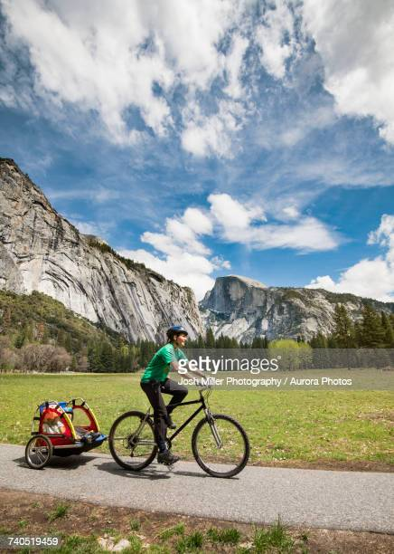female tourist with kids in trailer riding bicycle in yosemite national park - yosemite valley stock photos and pictures