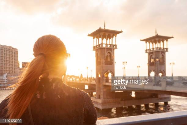 female tourist with red hair looking out over stanley bridge at sunset, rear view, alexandria, egypt - alexandria stock pictures, royalty-free photos & images