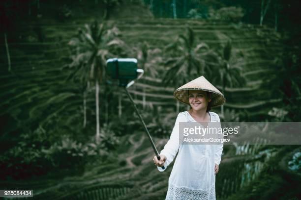 Tourisme femme avec chapeau de paille traditionnel prenant Selfie au champs de riz