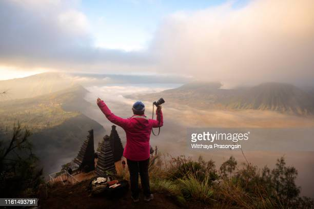 female tourists are standing at the bromo volcano in indonesia, traveling in asia. - mt semeru stock pictures, royalty-free photos & images