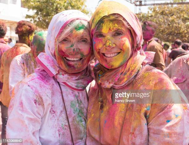 female tourists at hindu holi festival in india. - india stock pictures, royalty-free photos & images