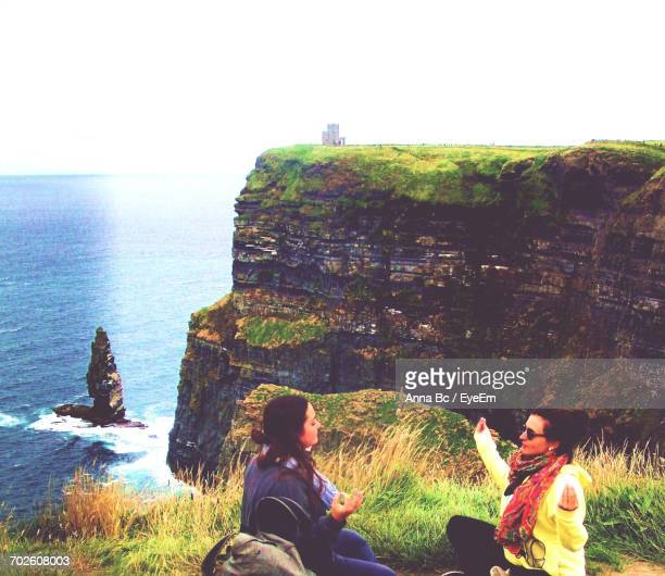 Female Tourists Practicing Yoga On Cliffs Of Moher