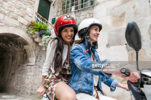 female tourists riding moped through village, split, dalmatia, croatia - moped stock photos and pictures