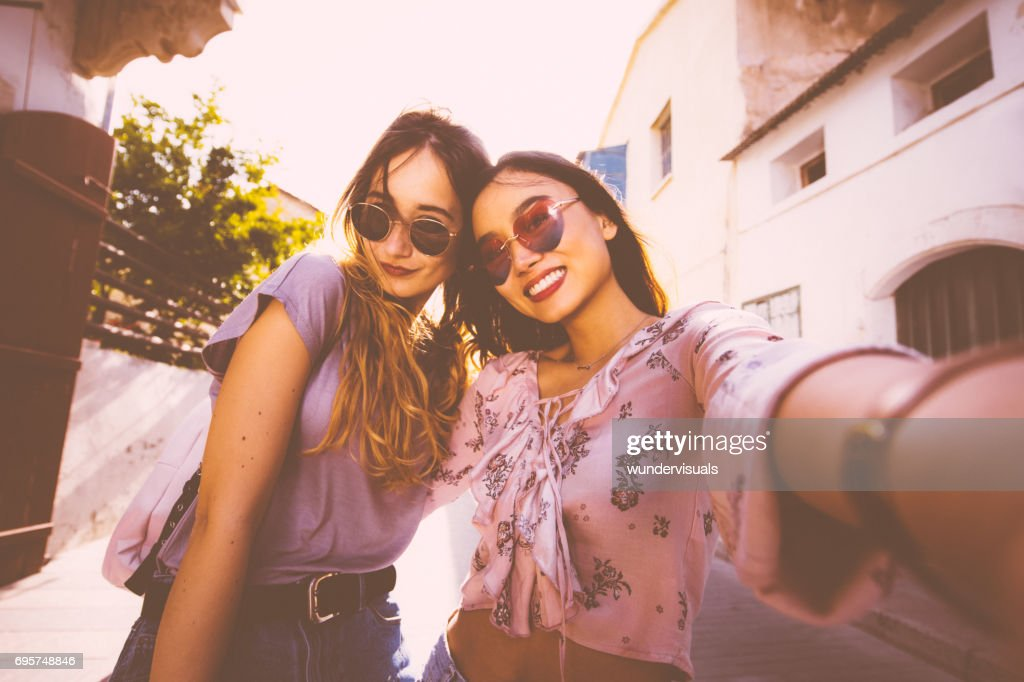 Female tourists taking a selfie in Italian old city streets : Stock Photo