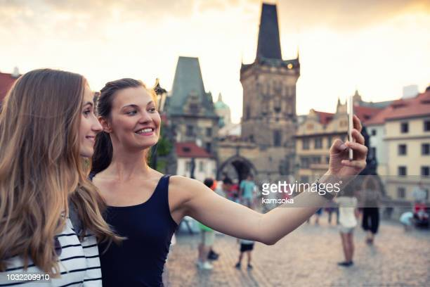 female tourists taking selfie on the charles bridge in prague - beautiful czech women stock photos and pictures