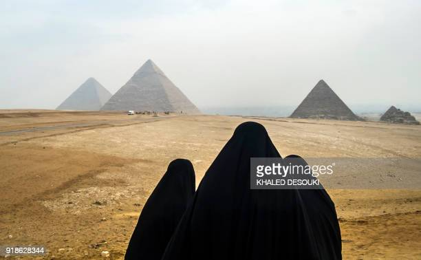 TOPSHOT Female tourists wearing veils look at the Pyramids of Giza as they stand from across the Giza plateau on the southwestern outskirts of the...