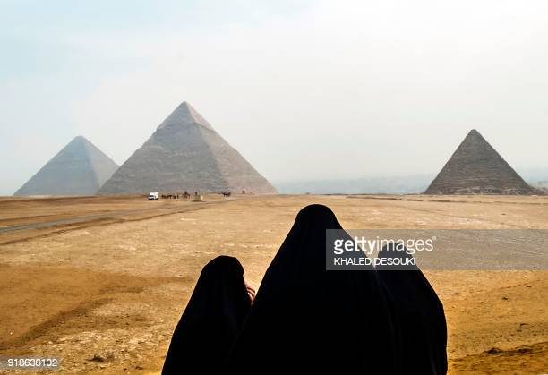 Female tourists wearing veils look at the Pyramids of Giza as they stand from across the Giza plateau on the southwestern outskirts of the Egyptian...