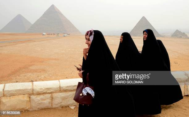 Female tourists wearing veils walk on the Giza plateau across from the Great Pyramids complex on the southwestern outskirts of the Egyptian capital...