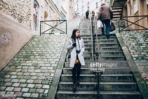A female touristy is walking down stairs