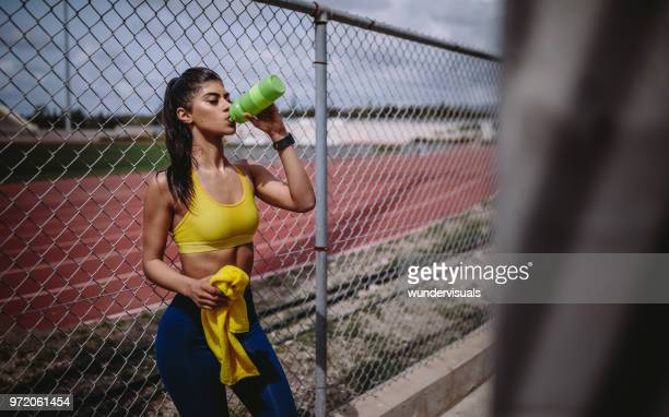 female track and field athlete drinking water after sports training - energy drink stock pictures, royalty-free photos & images