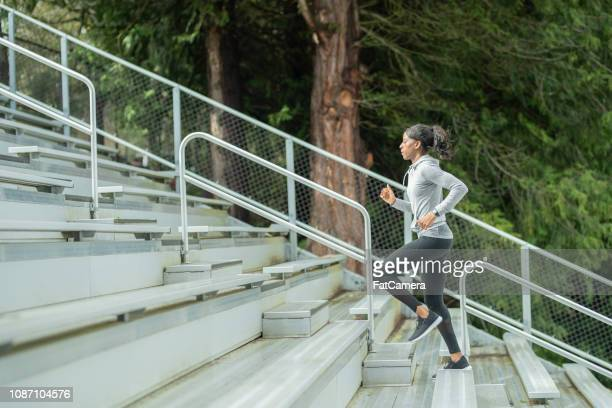 female track athlete trains on stadium bleachers - cardiovascular exercise stock pictures, royalty-free photos & images