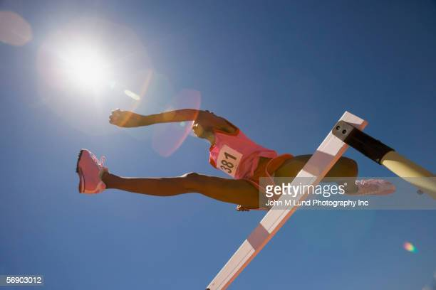 Female track participant jumping over hurdle
