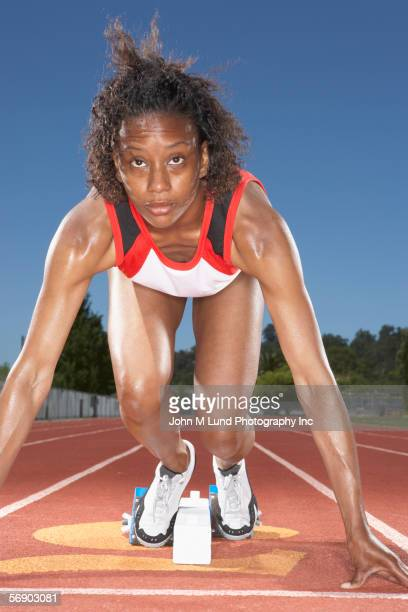 Female track runner preparing to race