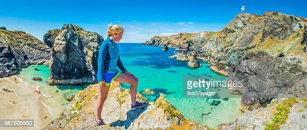 Female trail runner looking over idyllic ocean beach cliffs panorama