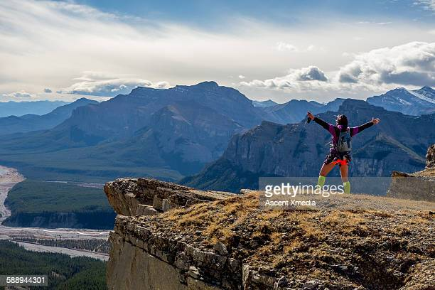Female trail runner stands on summit, arms out