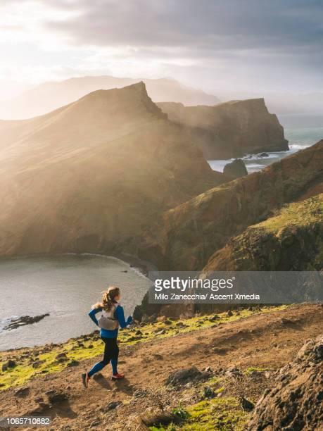 Female trail runner traverses trail above coastline, cliffs