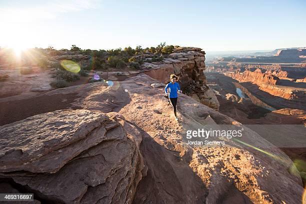 Female trail running on red rocks