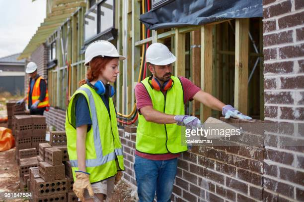 Female trainee looking at worker building wall