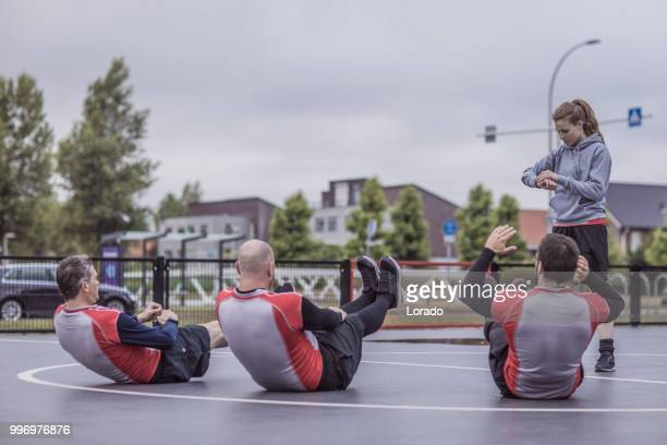 female trainer coaching a basketball team during a street ball training session - amateur stock pictures, royalty-free photos & images