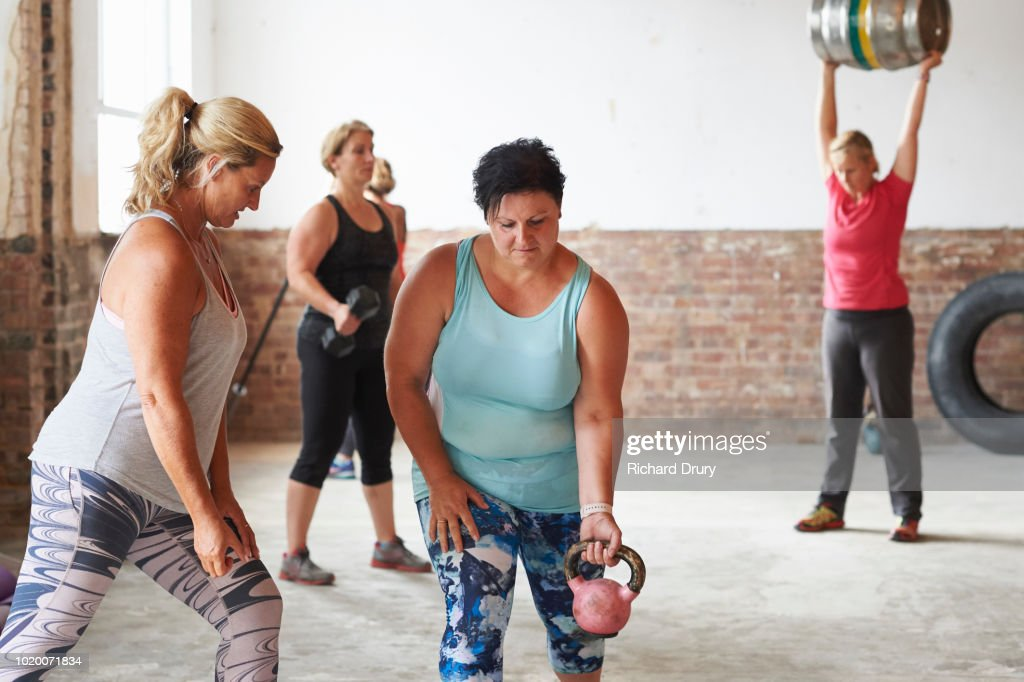 Female trainer working with woman lifting kettlebell in the gym : Stock Photo