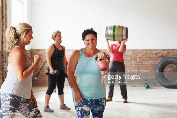 female trainer working with woman lifting kettlebell in the gym - richard drury stock pictures, royalty-free photos & images