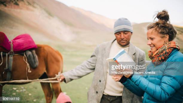 Female traveler asking local with horse for directions and advice