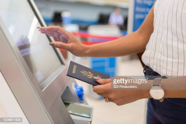 female traveler checks in at the airport - kiosk stock pictures, royalty-free photos & images