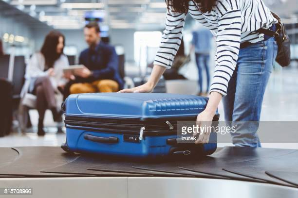 female traveler picking up suitcase from baggage claim line - baggage claim stock pictures, royalty-free photos & images