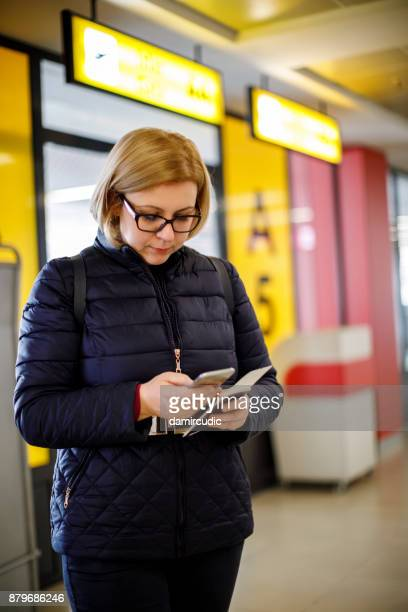 Female traveler using mobile phone while waiting for a flight