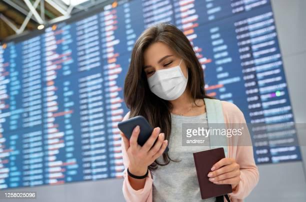 una viajera que lleva una máscara facial en el aeropuerto mientras envía mensajes de texto en su teléfono - journey fotografías e imágenes de stock